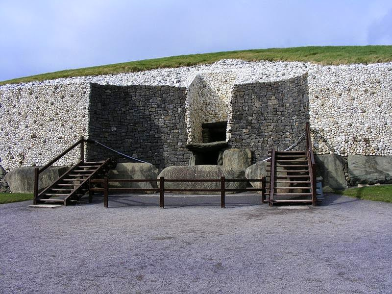 "Entrance to Newgrange. The original entrance was ""cut away"" when the wall was reconstructed to provide better access (and stop people climbing over the stone that originally blocked the entrance way). The rebuilt wall is faced in the original white quartz with darker river stones dotted about, with the cut away section in the darker stone. The ""window box"" that lets light into the mound on the Winter Solstice is above the shelf type structure, which sits above the entrance itself."