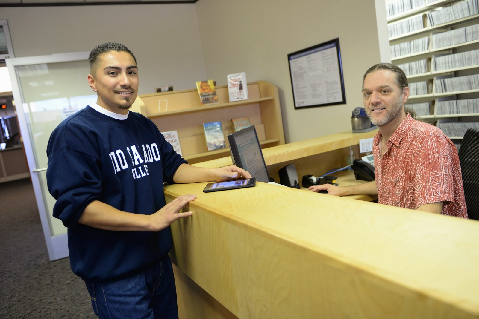 Image of two Rio Salado employees at a reception desk looking at the camera