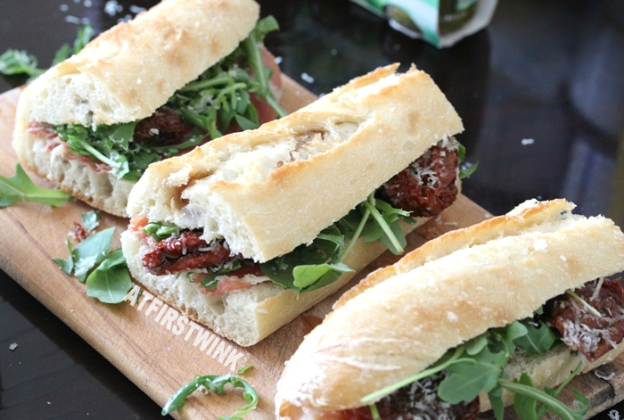 three baquettes with serrano ham, sun-dried tomatoes, peccorino, and rocket lettuce