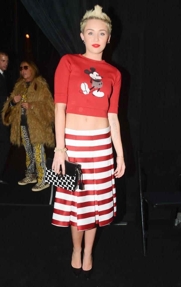 Miley Cyrus na Semana de Moda de NY. Ela usa um Moletom Cropped com Estampa do Mickey (Relembrando seus tempos de Disney...) e uma Saia Midi com Listras Horizontais.