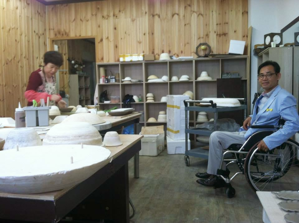 Image of man in wheelchair in pottery workshop with woman working at table