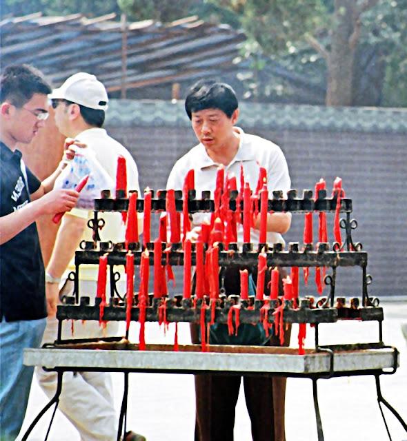people lighting candles for Buddha