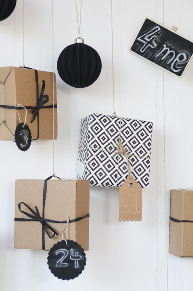 Adventkalender Geschenke in Packpapier und schwarzweißem Papier hängen an einem Ast