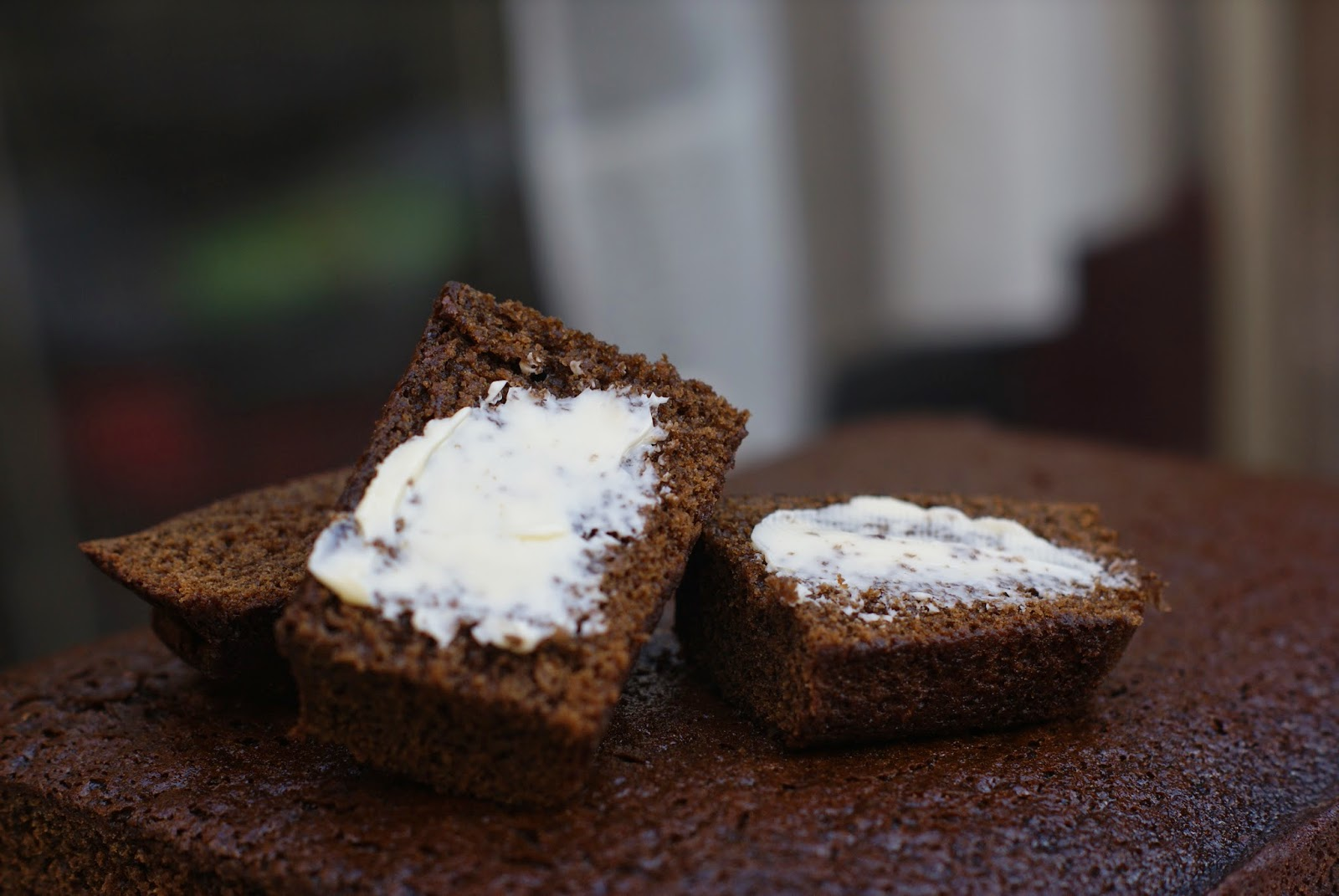 sticky gingerbread loaf with slices and butter on top of a slice with a knife to the side