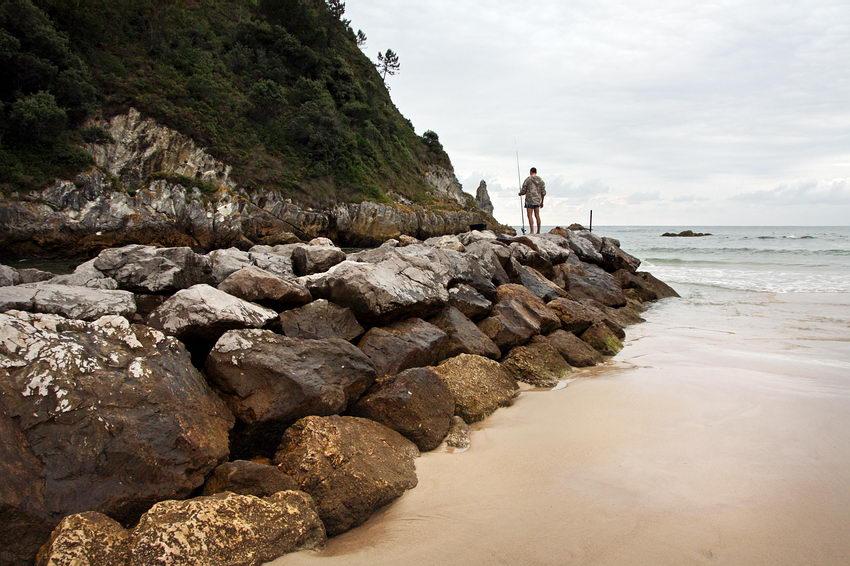 Pormenor da praia: Pedras de protecção ao avanço do mar, na esquerda e um pescador ao fundo com uma cana
