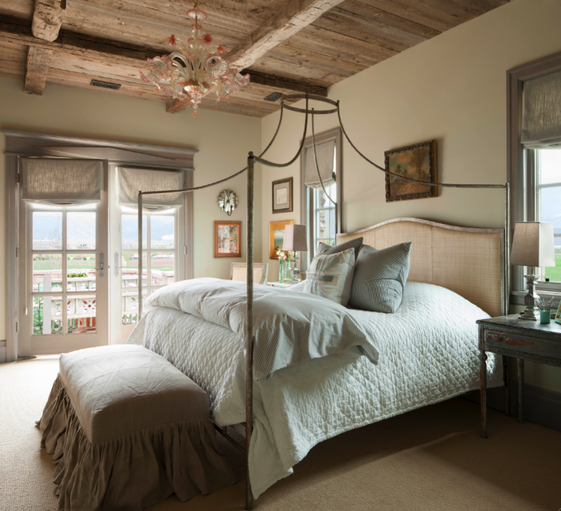 Bedroom with rustic wood ceiling. Come see this Rustic Elegant French Gustavian Cottage by Decor de Provence in Utah! #frenchcountry #frenchfarmhouse #interiordesigninspiration #rusticdecor #europeanfarmhouse #housetour