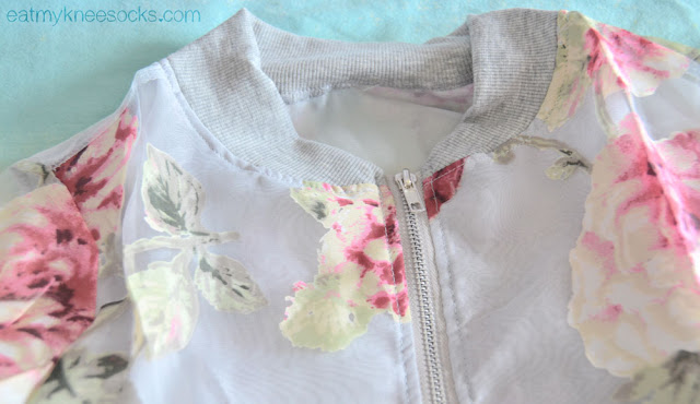 The gray trim on the neckline of the zippered organza floral jacket from Dresslink.