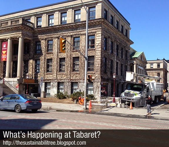 A landscaping truck sits in front of the Tabaret building