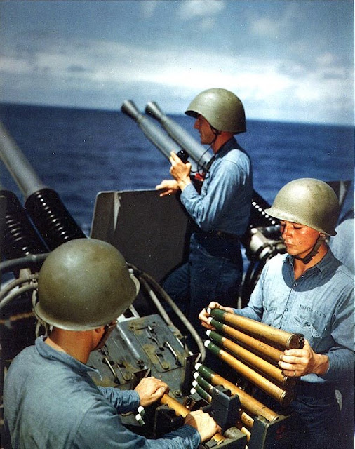 USS Alaska (CB-1): Crew of a 40mm quad antiaircraft machine gun mount loading clips into the loaders of the left pair of guns. Taken on 6 March 1945, during the Iwo Jima operation. The man at the right is Seaman Second Class Richard Roberts, and the gun captain (in the phone talker's helmet) is Gunner's Mate Second Class Glenn F. Groff.