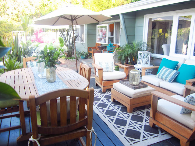 Deck with umbrella, wooden outdoor dining table and seating area with armchairs, bench and small ottoman style table