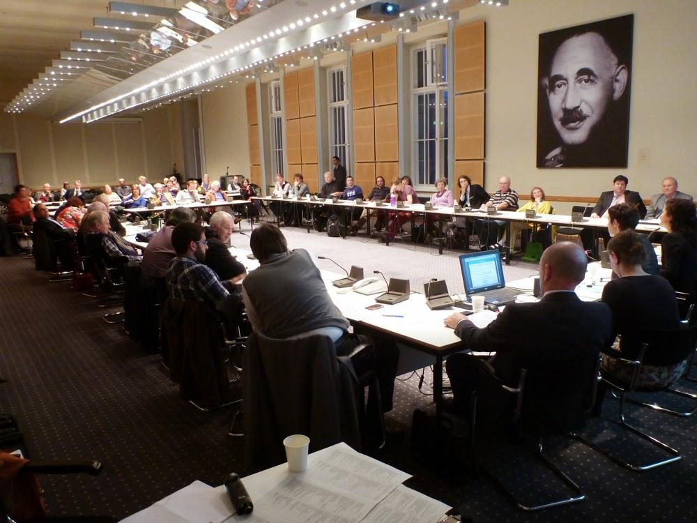 Sitzungssaal, Subjektive vom Dolmetschertisch mit Vokabelliste und Mikro. Pause. Die Kollegin dolmetscht ins Deutsche