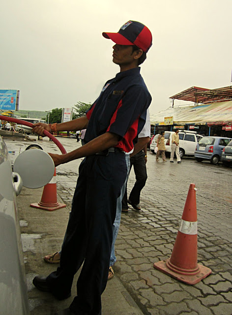 petrol pump attendant filling petrol in car