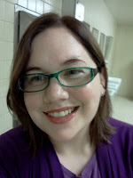 Self-portrait headshot of the author.  Dark auburn hair that hits the shoulders, green rectangle glasses, fair skin, smiling, with medium pink lip gloss. Wearing light purple shirt with darker purple cardigan