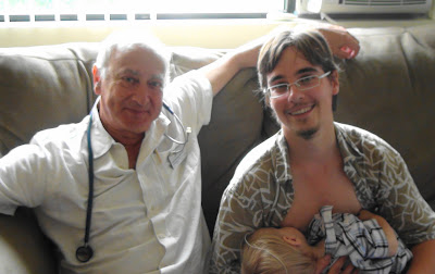 Dr. Newman, wearing a stethoscope, sits beside me on a couch as I nurse Jacob.