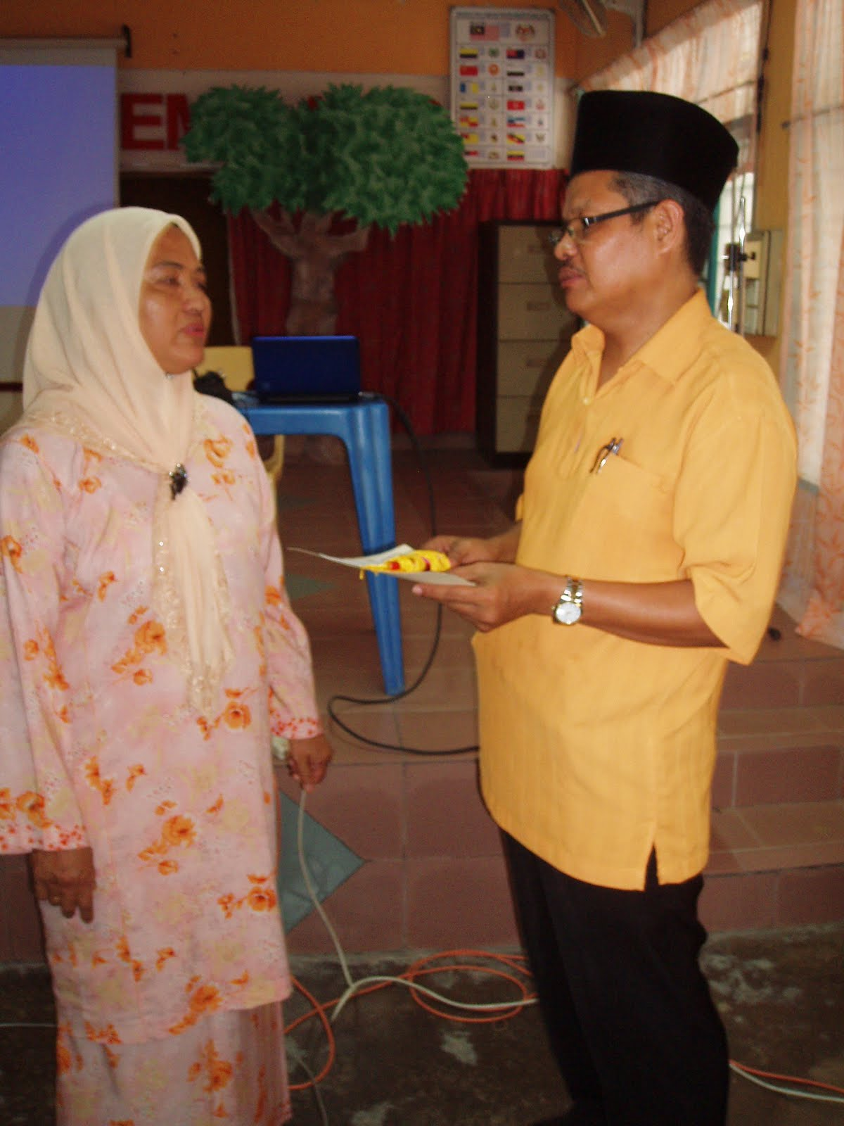 Cikgu Rozali Bin Rajab menerima cenderamata daripada Pn Pengetua SMK