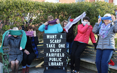 Five women, holding scarves that conceal their faces, stand next to and behind a sign that reads, 'Want a scarf / Take one / Enjoy / Fairfield Public Library'