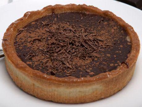 Makkelijke chocoladetaart met cacaopoeder in de blind gebakken taartkorst, gevuld met ganache en afgewerkt met cacaopoeder en geraspte chocolade