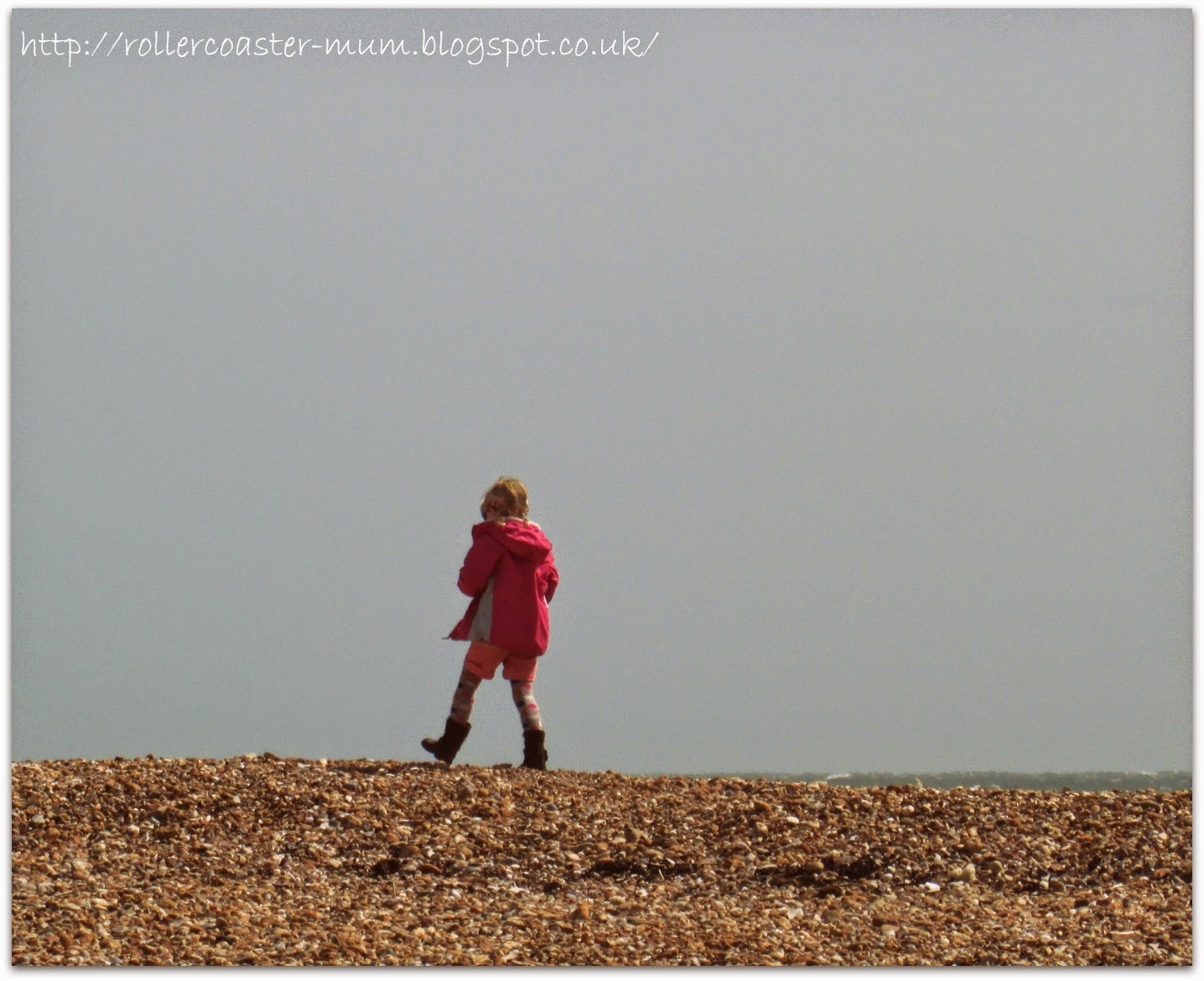 Braving the wind on a pebbly beach, Hayling Island