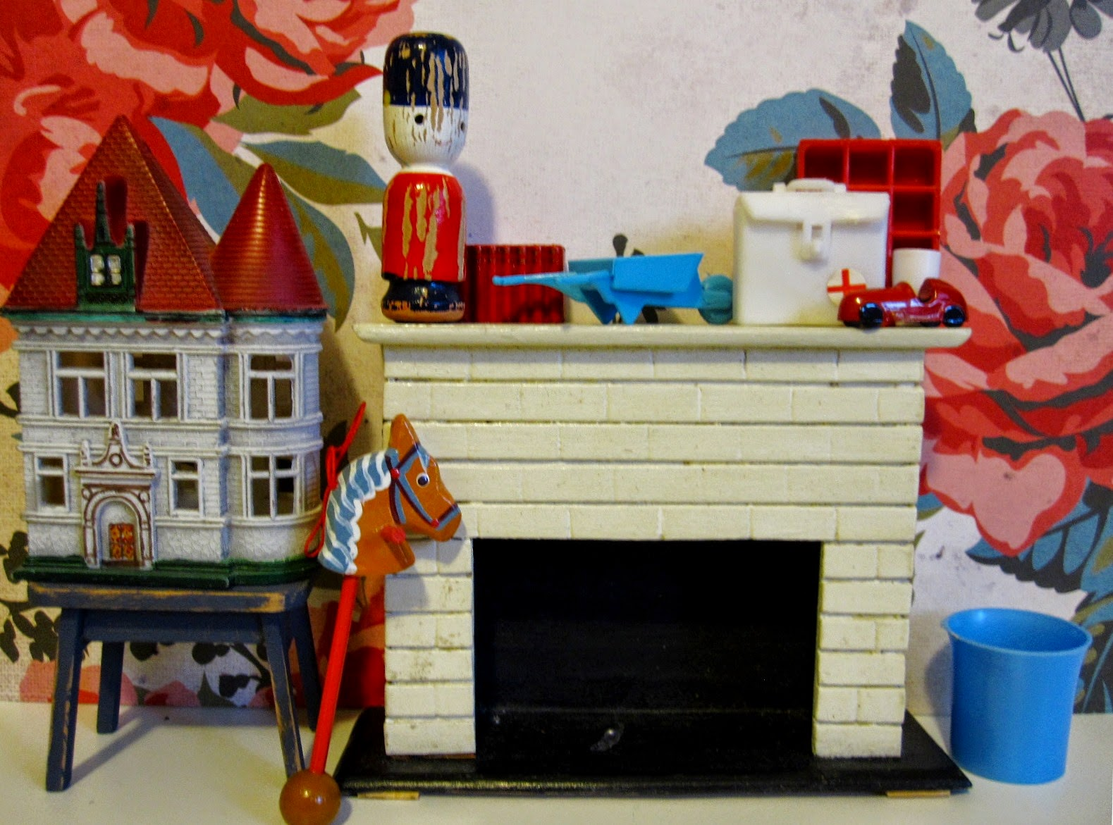 Selection of vintage miniature accessories displayed around a dolls' house mantlepiece. Colours are predominantly red, cream and mid=blue.