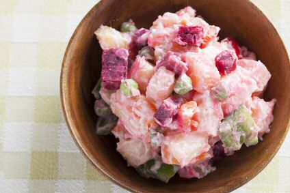 Een bord met rode bieten salade, aardappels en een yoghurt dressing met verse tuinkruiden