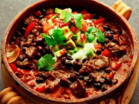Lekkere chili con carne geserveerd met stukjes avocado en korianderblaadjes