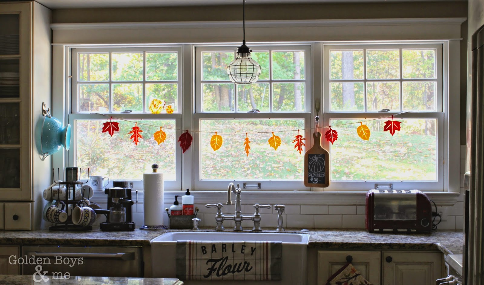 Triple window over farm sink in kitchen with fall leaf garland-www.goldenboysandme.com