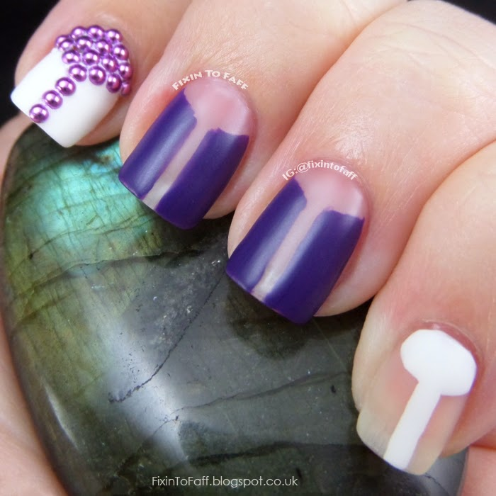 Nail art based on a 1960s mod theme, featuring negative space patterns and purple studs.