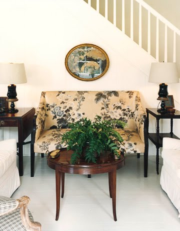 Living room in a colonial home with a chintz English settee between two black side tables with a round, wooden coffee table in front