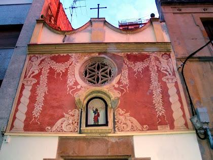 Detall de la façana principal de la capella de Sant Joan decorada modernament amb esgrafiats de l'artista local Jaume Amat. Podem observar la fornícula amb la imatge de Sant Joan Baptista, i una rosassa amb una flor de sis pètals