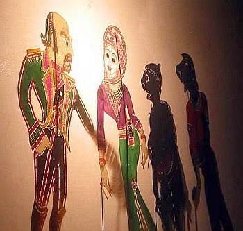Fascinating story: A tourist (left) being greeted by a local woman as part of the wayang kulit characters.