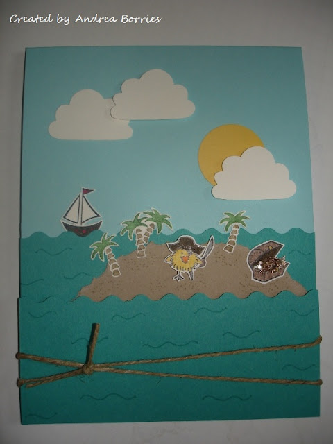 Light blue card with layered teal card stock scalloped like waves. A light brown island has stamped and cut-out palm trees, pirate chickie and treasure chest (with glitter treasure). There is also a sailing boat, clouds and sun.