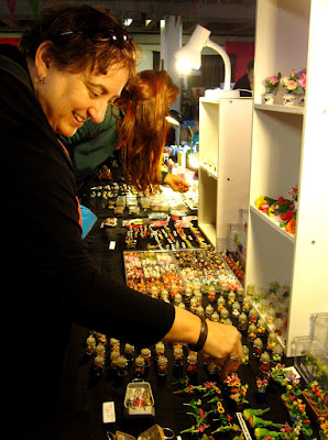 Woman browsing the goods for sale at a market stall selling dolls' house miniatures.