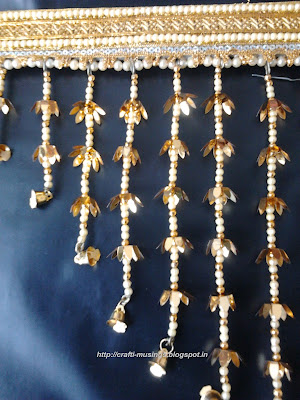 Closeup of the one half of the hanging strings of beads with golden flowers