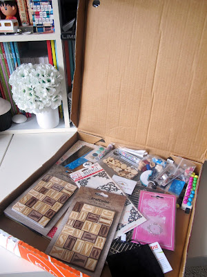 Opened pizza box, showing a range of paper craft supplies.