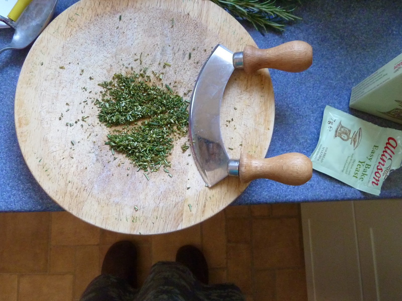 Freshly chopped rosemary on board with rocking knife