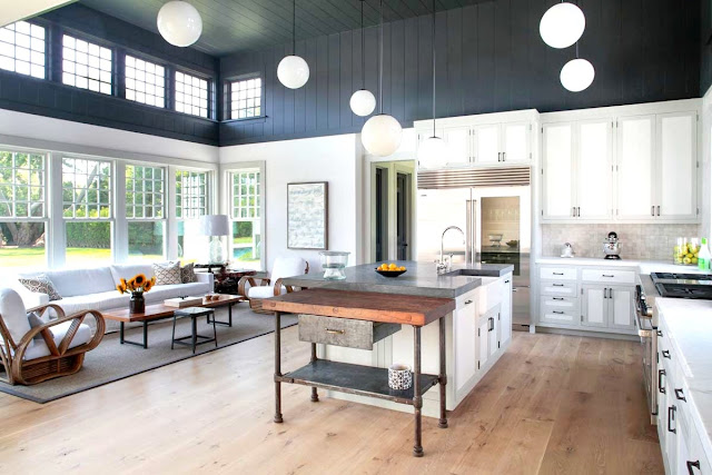 Farmhouse style kitchen with grey and white color blocked walls, pine wood floors, rattan furniture and white pendant lights