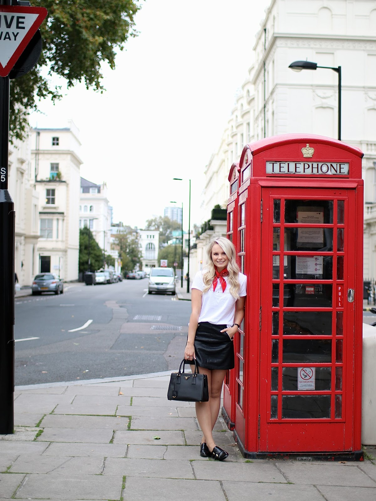 a blonde women with loose curls stands next to red telephone booth in london, notting hill