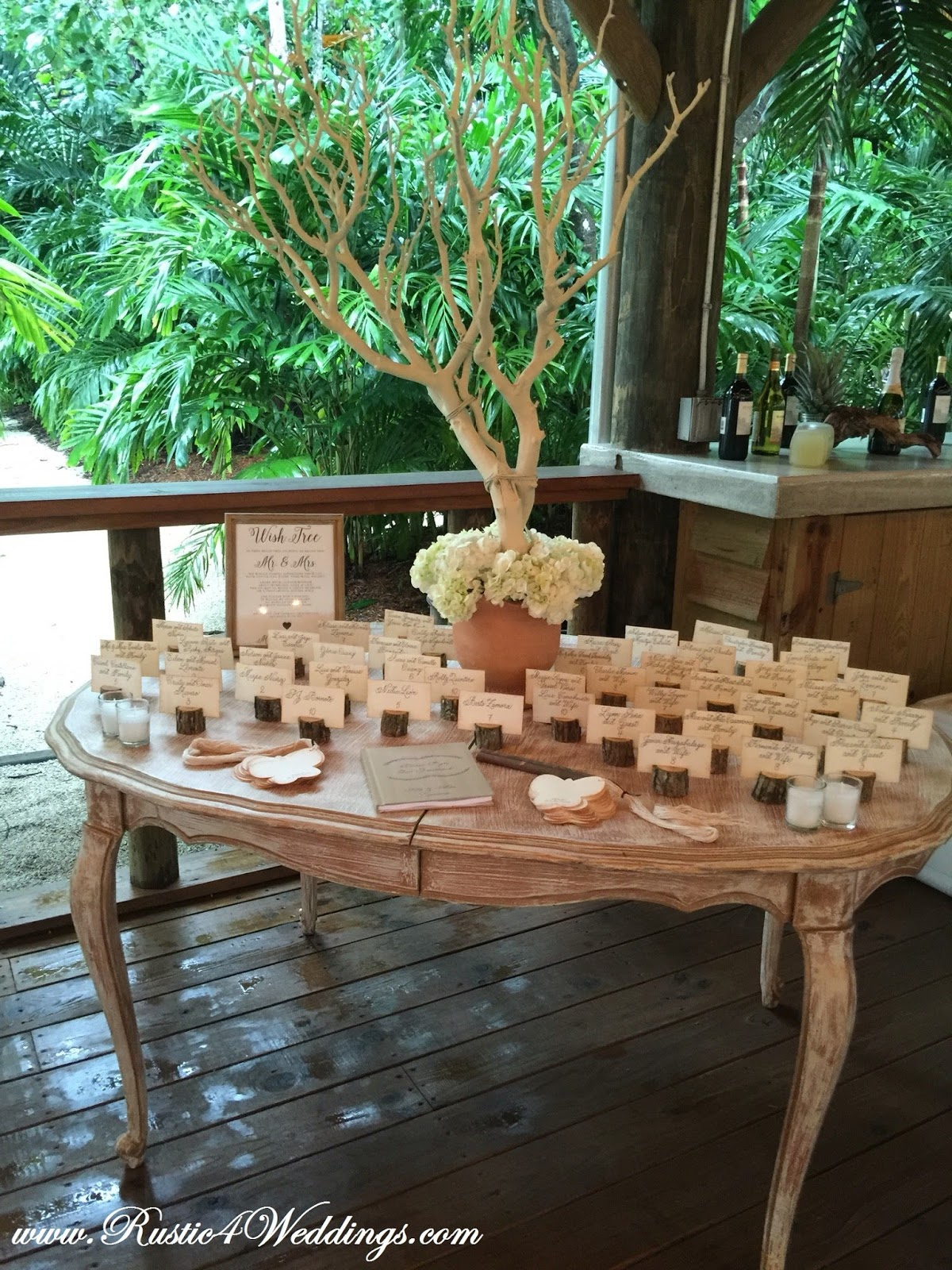 rustic beach wedding with table and rustic tree branch place card holders