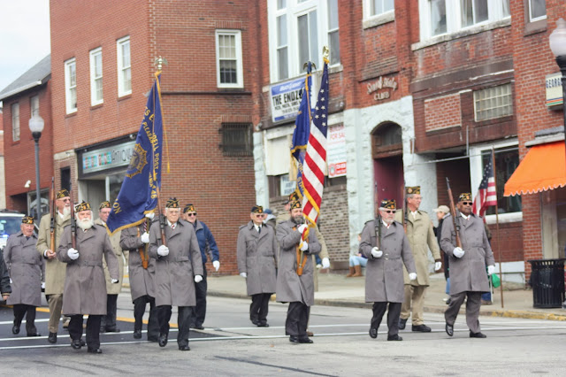 Veterans marching down main street with American and legion flags
