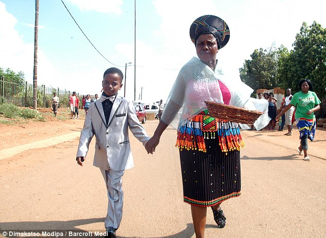 Given away: Sanele walks to his wedding with his mother as people look on. The ceremony shocked some people in the community.