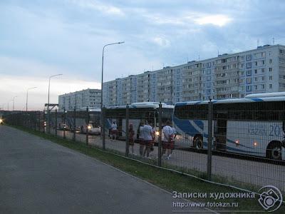 За оградой автобусная посадочная площадка Деревни Универсиады