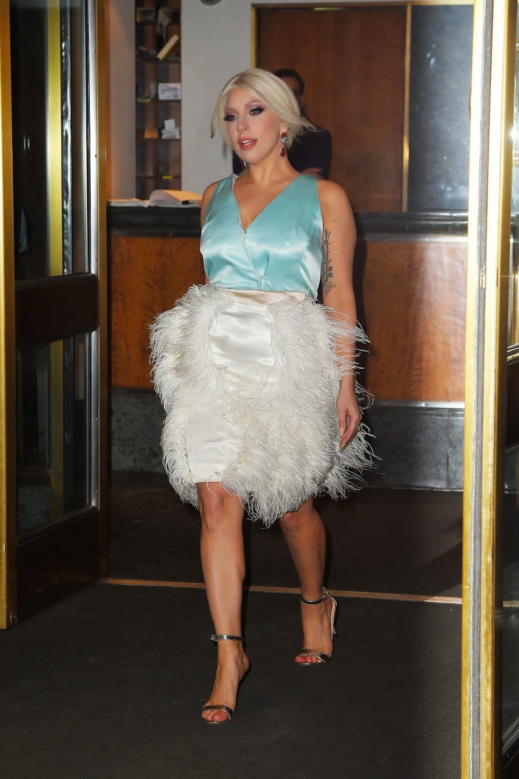 Lady Gaga spotted in a braless satin top and a fur fringed skirt in New York City