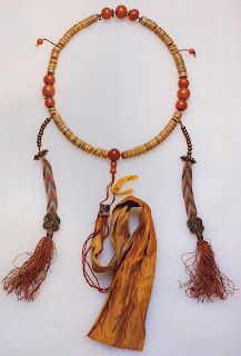 A Buddhist mala. The 108 disk-shaped prayer beads are made from the bones of a lama (holy man). The dividers and retaining beads are coral, and the tassels are silk. The sattin ribbon is partially covered with Tibetan writing. The two counters, each with ten silver beads, terminate in thunderbolt pendants (djore). Several hundred old, this mala belonged to Lama Kunga in Rinpoche of the Ngor monastery. Length (side to top center bead). 40 cm. Collection Ivory Freidus