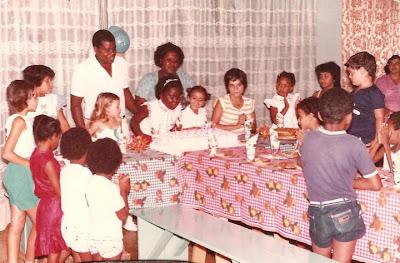 descrição da foto: festa de aniversário. várias crianças reunidas ao redor da mesa. Eu, ao centro, apagando sete velas colocadas em linha reta sobre um enorme bolo quadrado branco com rosa. Atrás de mim meu pai e minha mãe me observam sorrindo. A minha direita, ao lado de uma menina pequena está Isabel, menina de pele clara, cabelos curtos e escuros, é a única que olha para a câmera.