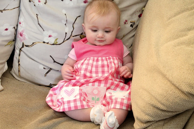 baby girl sat on sofa wearing a pink & white gingham dress with block pink at top and teacups on the bottom
