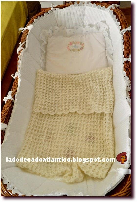Foto de um berço em vime, com protetor em gorgurão branco com renda, travesseiro (almofada) bordada e uma manta de tricô