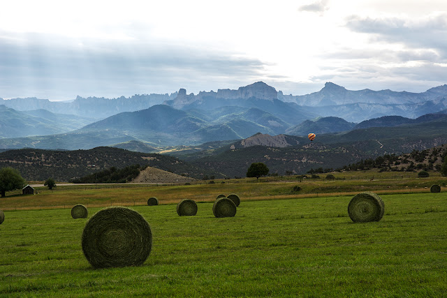Parting shot of the Cimmarrons with hot air balloon and sunbeams in a farm field of hay.