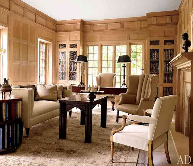 Home Office/Library with wood panelling, a fireplace, dark wood desk, accent table and coffee table, and a neutral sofa with matching armchairs