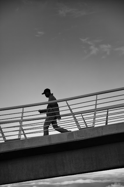 A man walks across a pedestrian bridge in Cape Town giving the appearance of being above the clouds