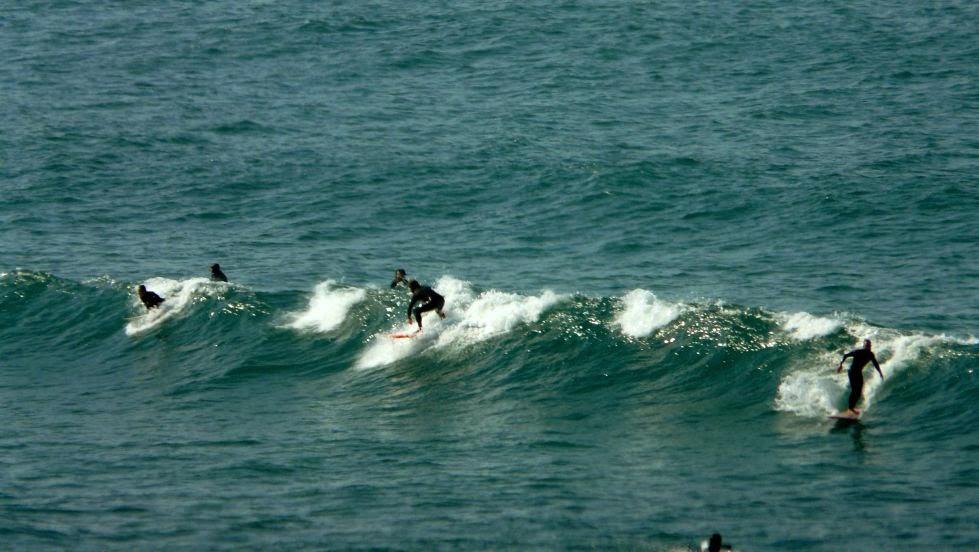 tres surfistas en la misma ola